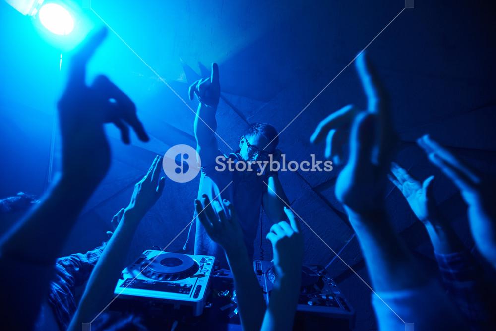 Deejay with headphones enjoying music among energetic dancers