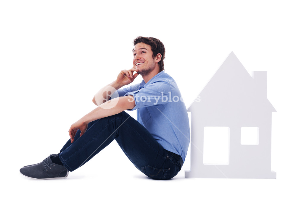 Dreaming man sitting next to a sign home