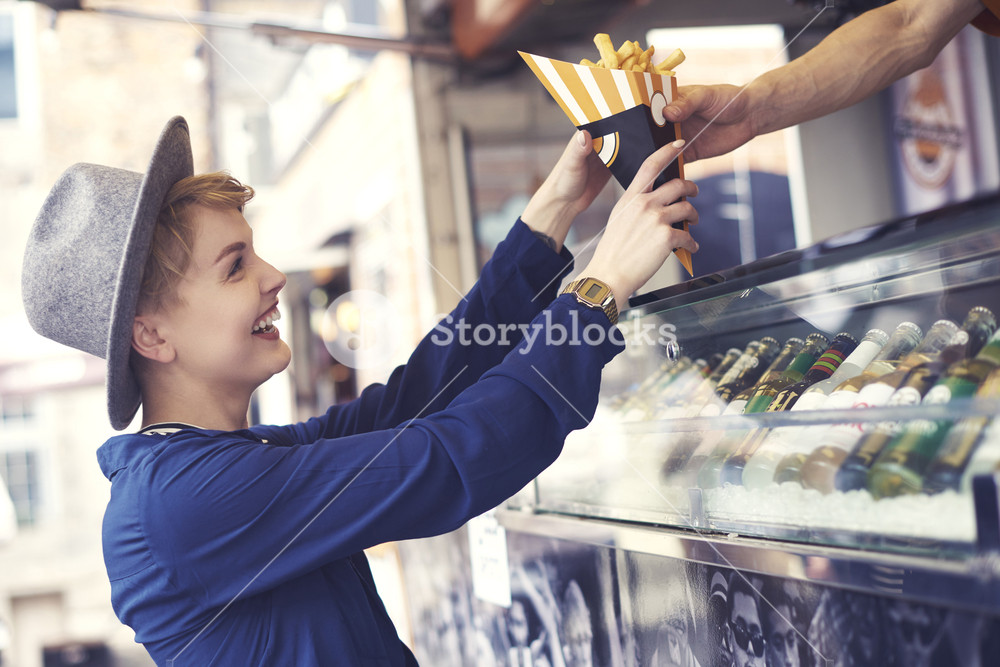 Female customer reaching food from vendor