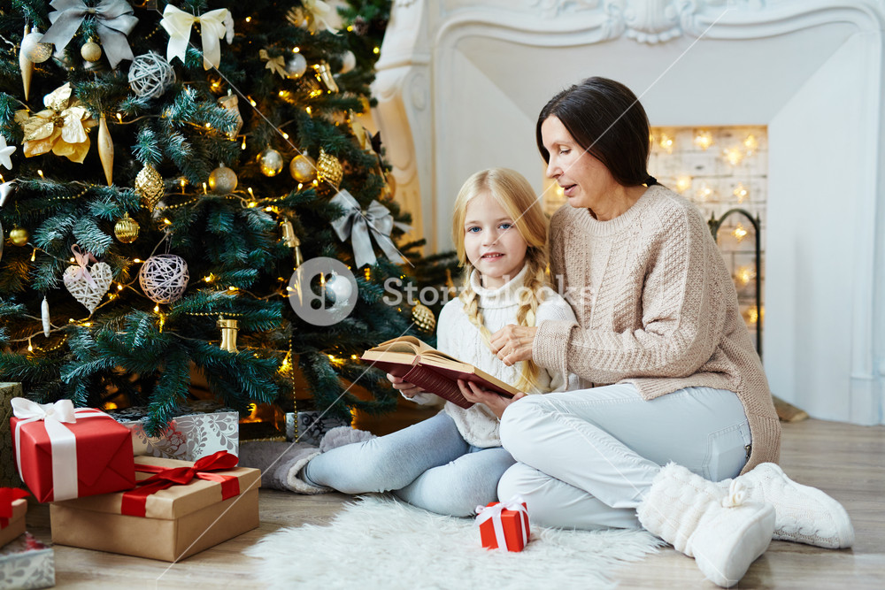 Granny and little girl reading Christmas stories by decorated firtree