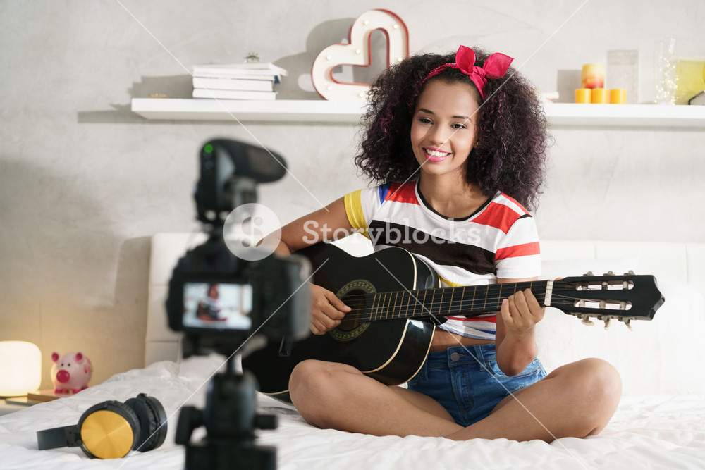 Happy black girl at home playing guitar. Young African American woman working as web influencer, recording vlog and music tutorial for the Internet.