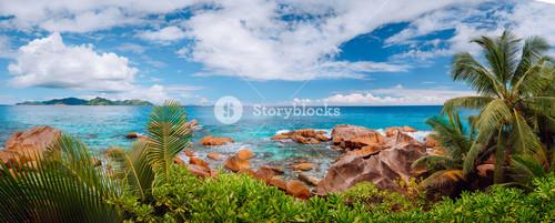 Impressive cloudscape panorama of La Digue wild rocky shore and Praslin Island on horizon. Seychelles.