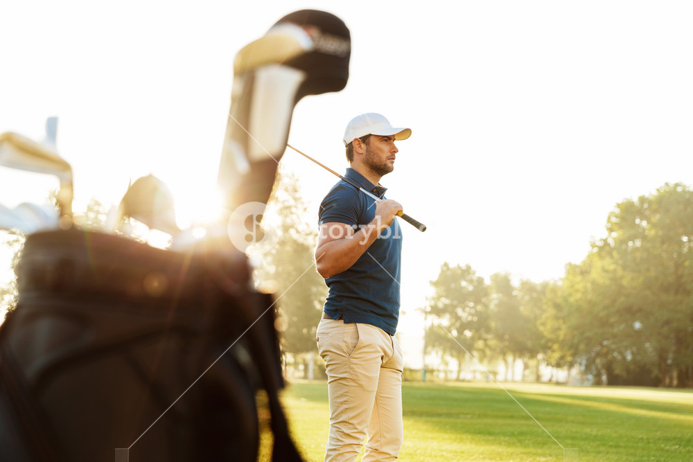 Male golfer holding driver while standing on green course