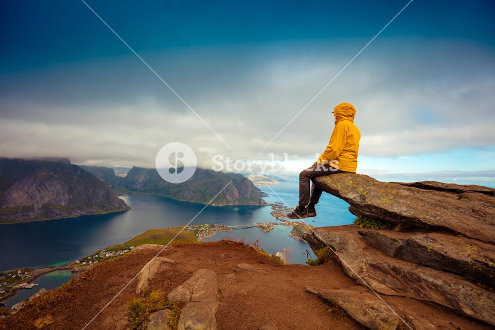 Male tourist sitting on the cliff. Beautiful mountain landscape of Lofoten islands, Reine, Norway.