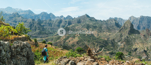 Man hiker walking among remote mountainous landscape with agriculture terraces in vertical valley sides. Santo Antao Island, Cape Verde
