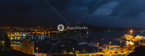 Mindelo in dusk light. Port town with many boats in the bay on the Cape Verde in the northern part of the island Sao Vicente. Long exposure panoramic shot of the bay