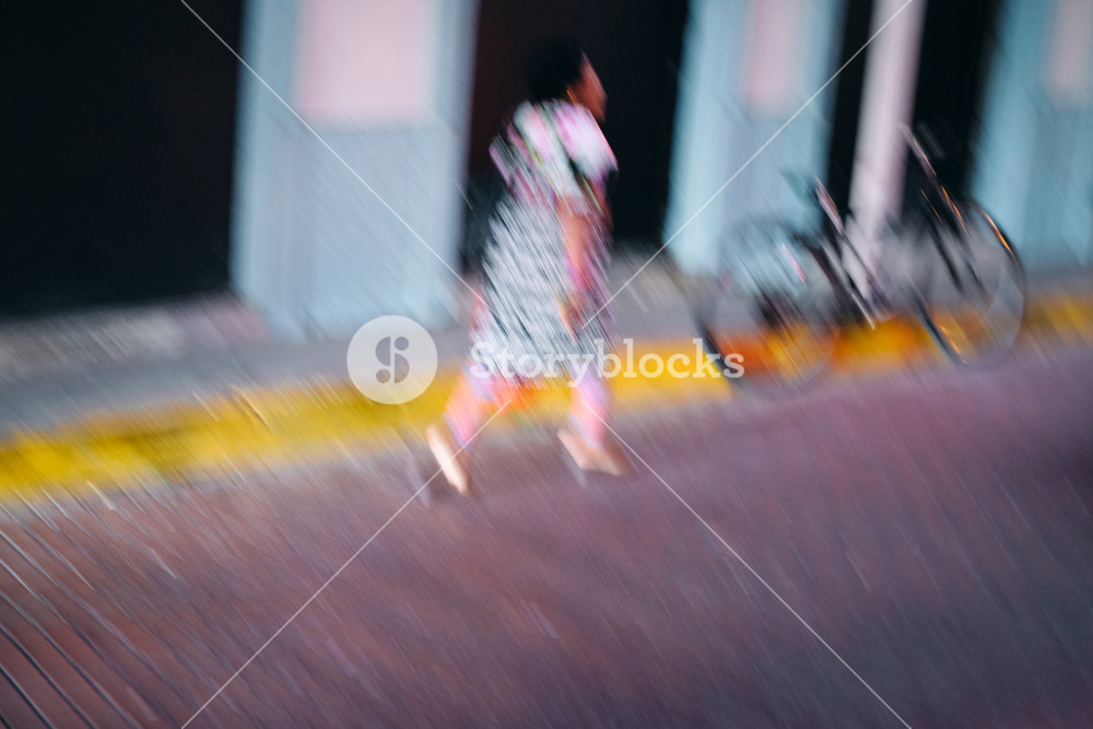 Motion blurred woman wearing traditional Guna Yala clothings, walking through the streets of Casco Antiguo in Ciudad de Panama, Central America