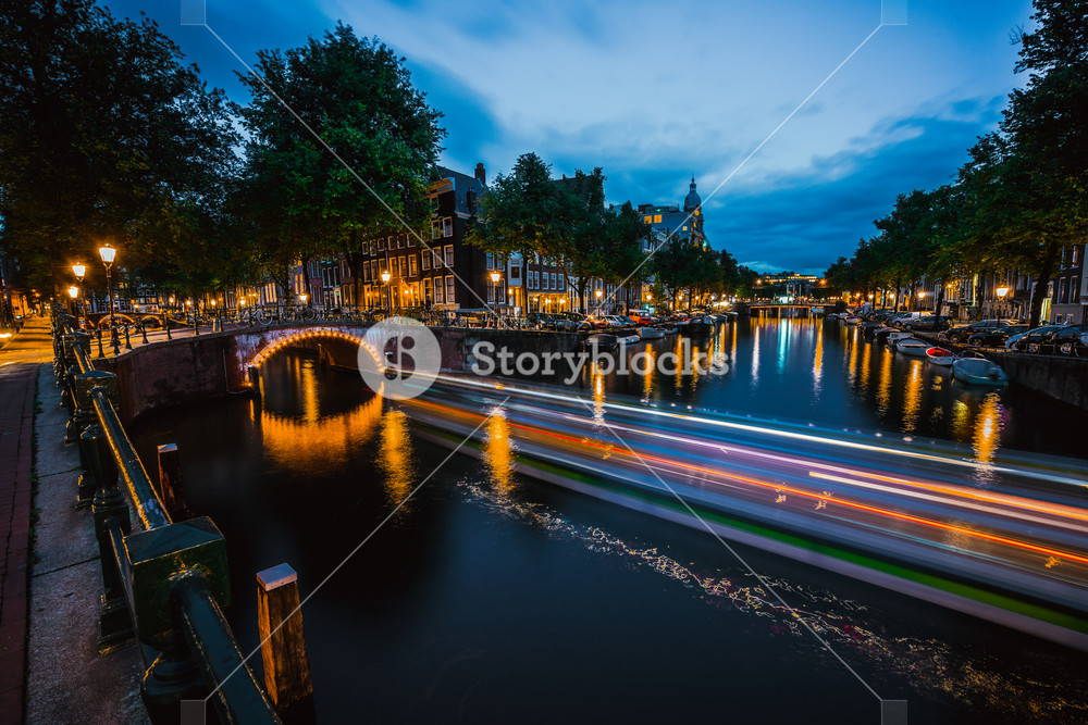 Night in Amsterdam. Lights trails and illuminated bridges on city canal at twilight. Holland, Netherlands. Long exposure