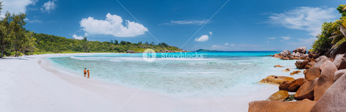 Panoramic shot of wide picturesque white sand beach, Seychelles, La Digue, Anse Cocos. Couple enyoing vocation time concept