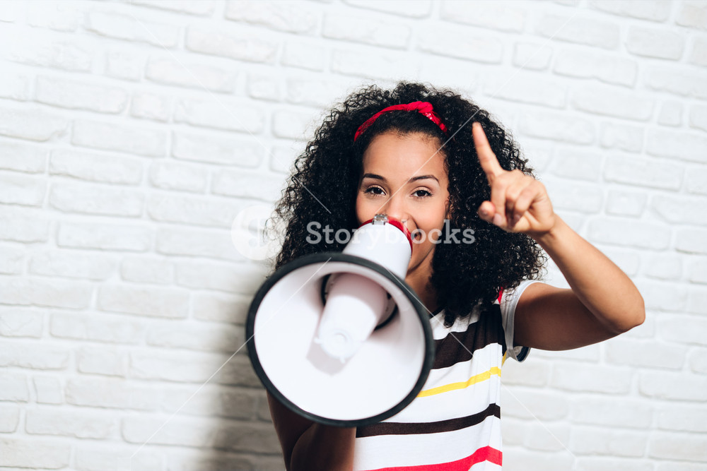 Portrait of happy african american woman shouting with megaphone for promotion, advertising. Black girl smiling and laughing for fun, joy, happiness