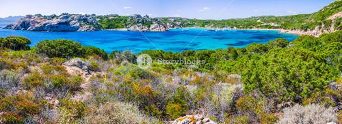 Sea bay with azure blue water surrounded by rocks on coast of Maddalena island, Sardinia, Italy