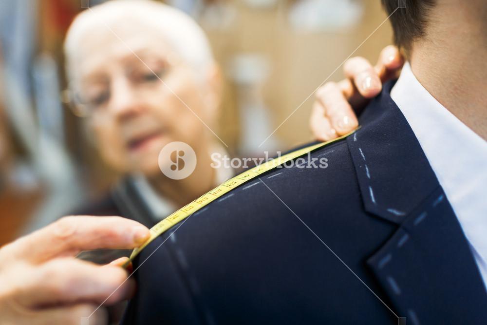 Shoulder of businessman in jacket visiting tailor