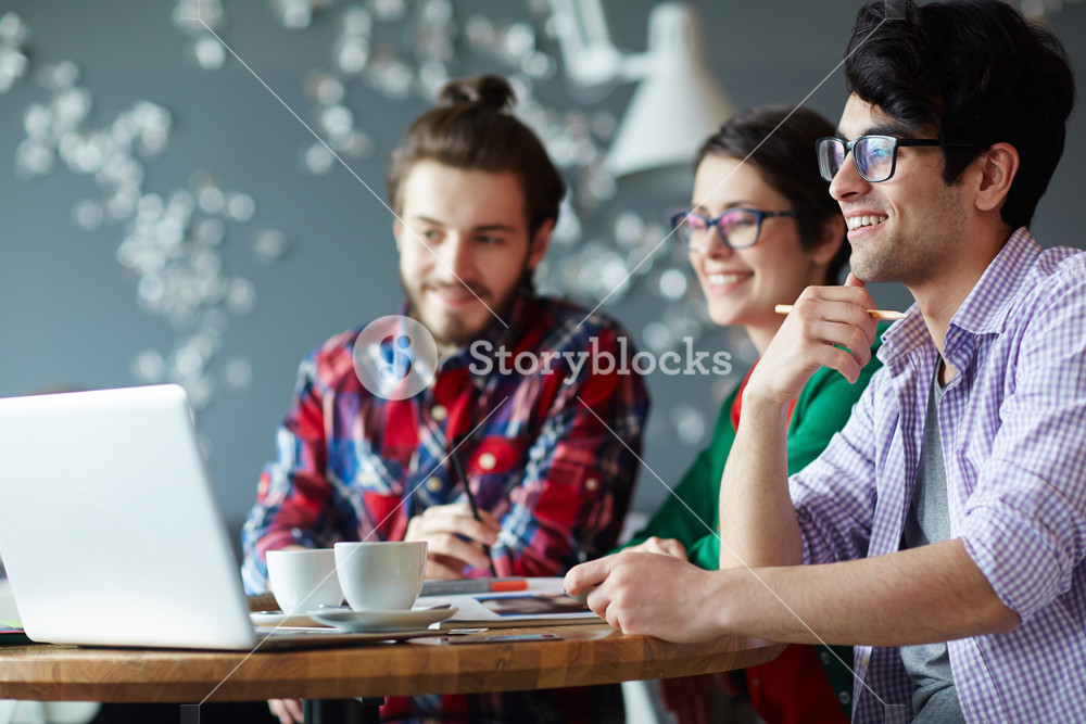 Side view of group of young creative people wearing casual clothes collaborating at meeting in office and smiling looking at laptop screen