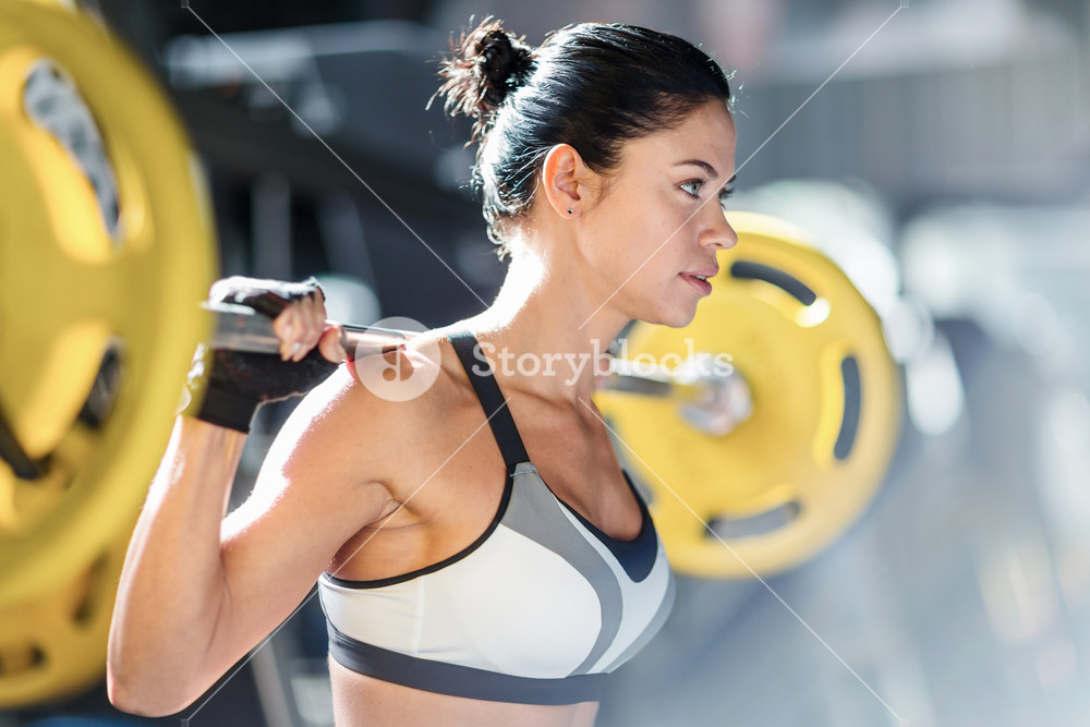 Side view portrait of beautiful muscular woman wearing sportswear doing weightlifting exercise holding big heavy bar on shoulders in modern gym