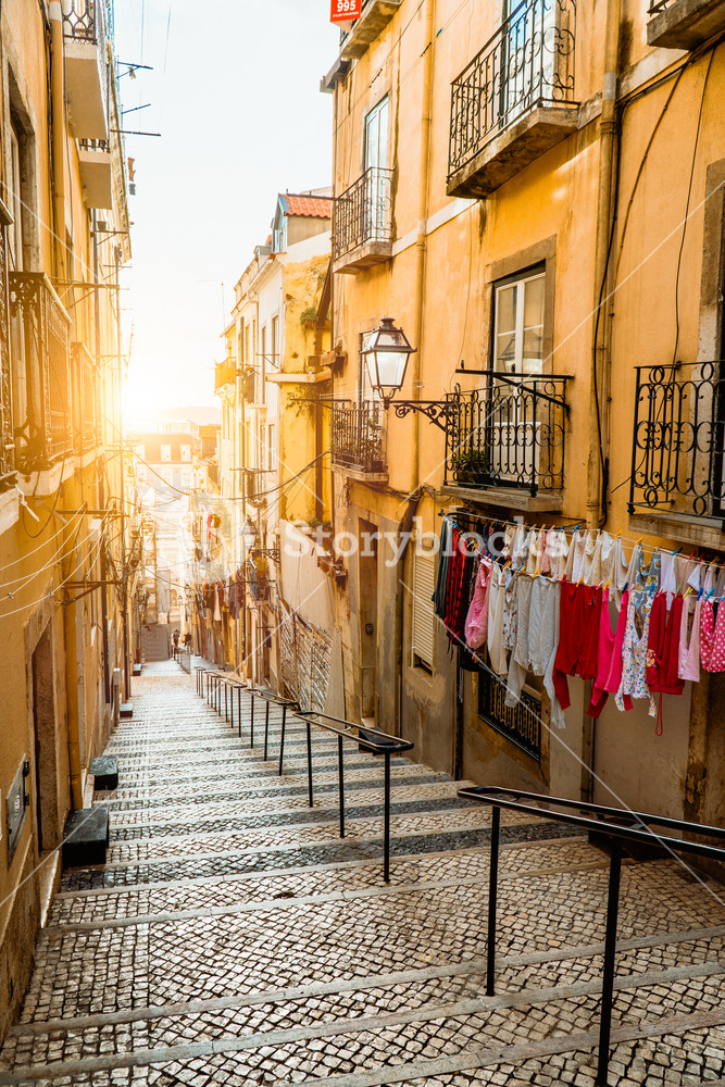 Staircase in the cobblestone street in Lisbon. Hanging laundry in typical narrow street. Sunset in the old downtown of Lisbon, impressions of the city. Lissabon