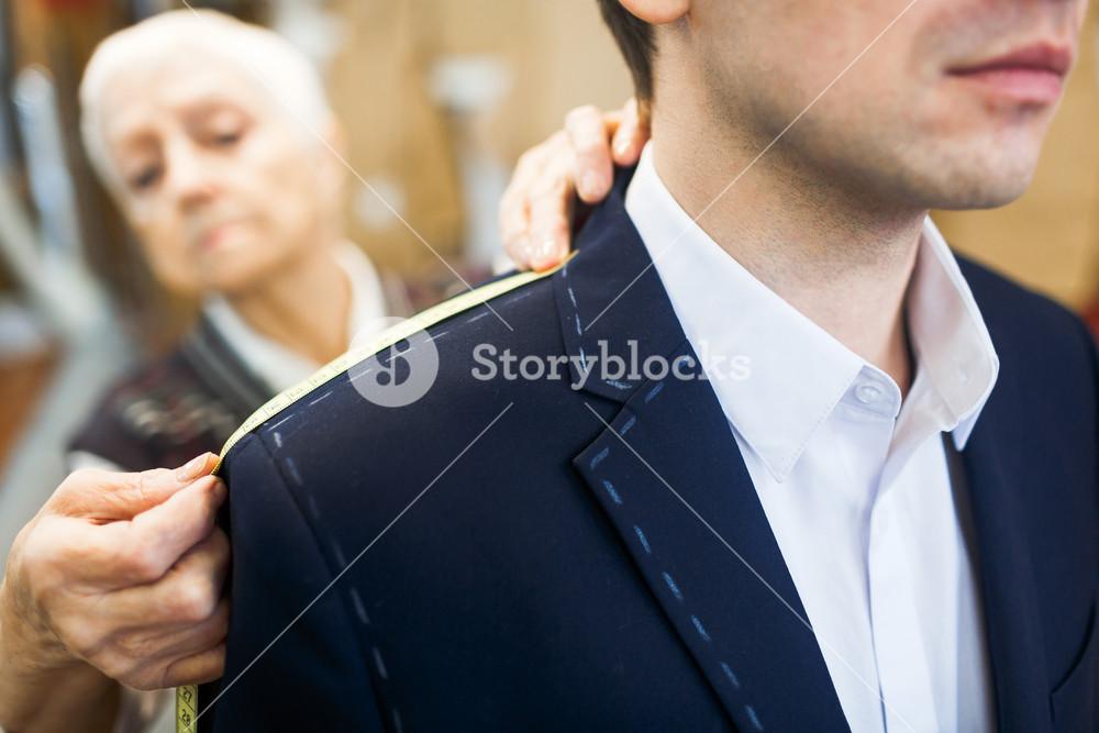 Tailor measuring shoulder length of male jacket