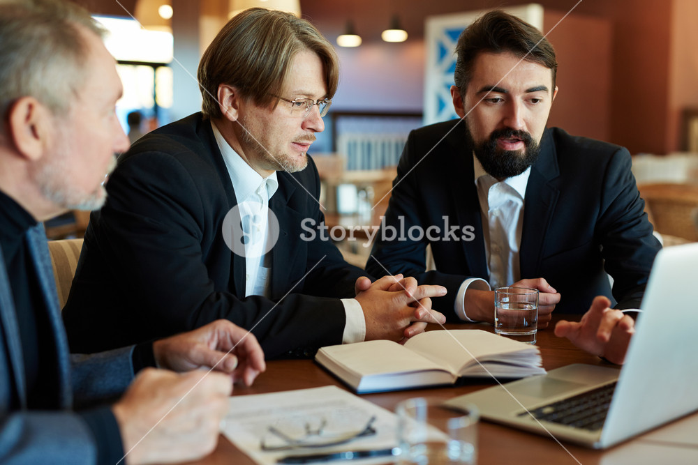 Teamwork of three bearded managers: they gathered together in cozy cafe and analyzing results of accomplished work, waist-up portrait