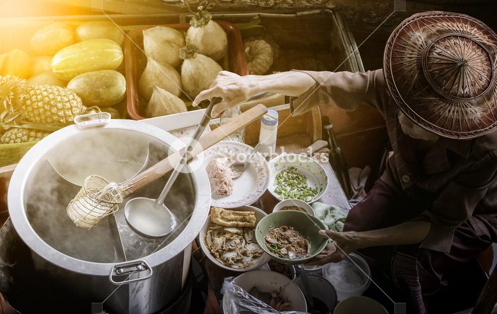 thai noodle food making on floating boat in floating market thailand