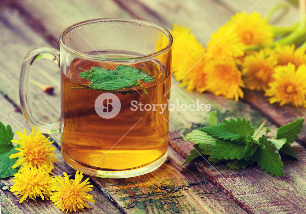 The cup of melissa herbal tea on a wooden table