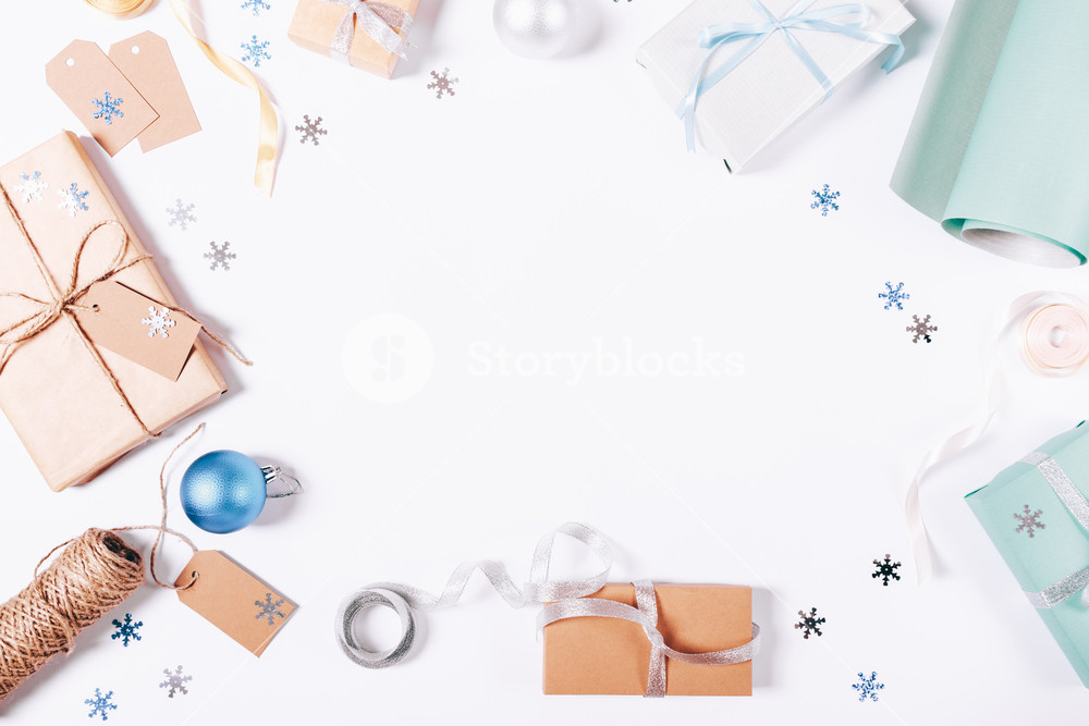 Top view of a box with a gift and Christmas decorations on a white table