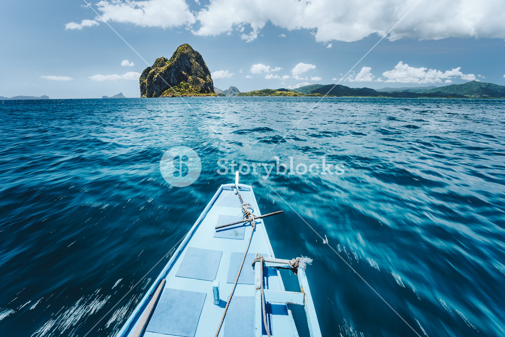 Traditional banca boat arriving amazing Pinagbuyatan Island. A small circular island with huge limestone cliffs and one tiny Ipil beach with coconut palm trees. El Nido, Palawan, Philippines