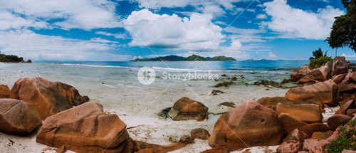 Tropical rockbound panorama landscape with white fluffy clouds above Praslin island. Anse Severe beach on La Digue island, Seychelles
