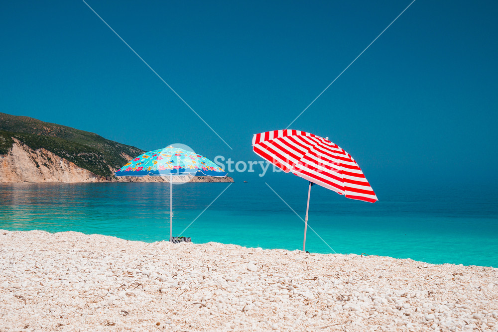 Two bright colored sun beach umbrella on pebble beach against turquoise blue sea water surface and clean blue sky