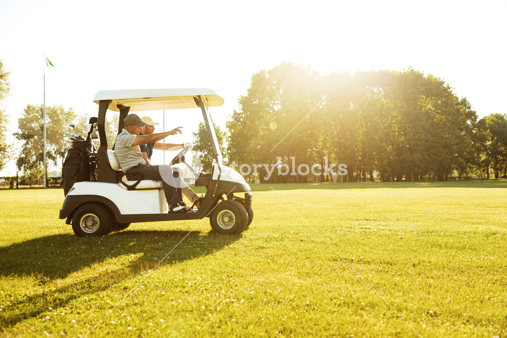 Two male golfers driving in a golf cart along green course