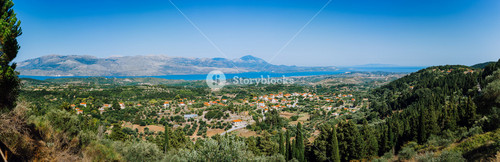 Ultra wide panormaic view of idyllic valley town with red roofs on mediterranean island. Olive groves, cypresses and blue bay in the distance