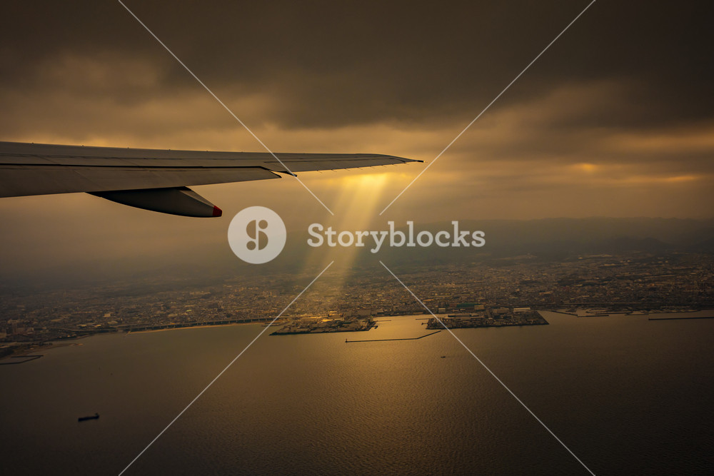view from plane window of sun light ray over osaka city japan