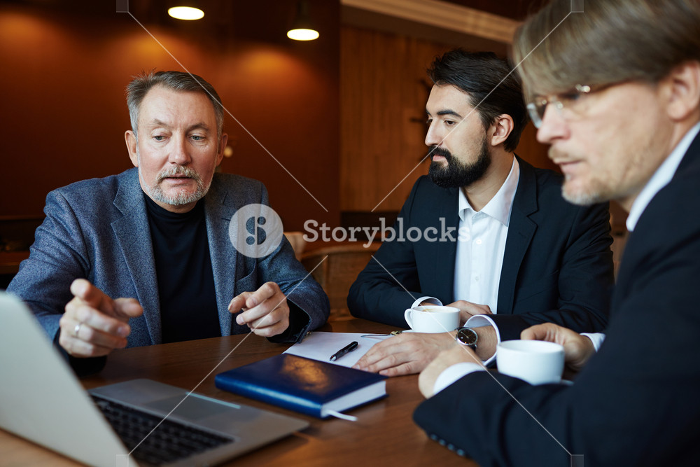 Waist-up portrait of bearded entrepreneurs analyzing risks and benefits of project investment with help of modern laptop while gathered together in dim cafe