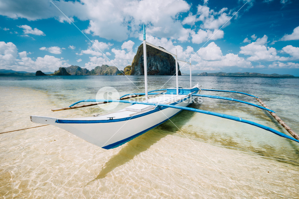 White banca boat on the sandy beach ready for island hopping trip. Amazing Pinagbuyutan island in background. Beautiful landscape scenery in El Nido, Palawan, Philippines