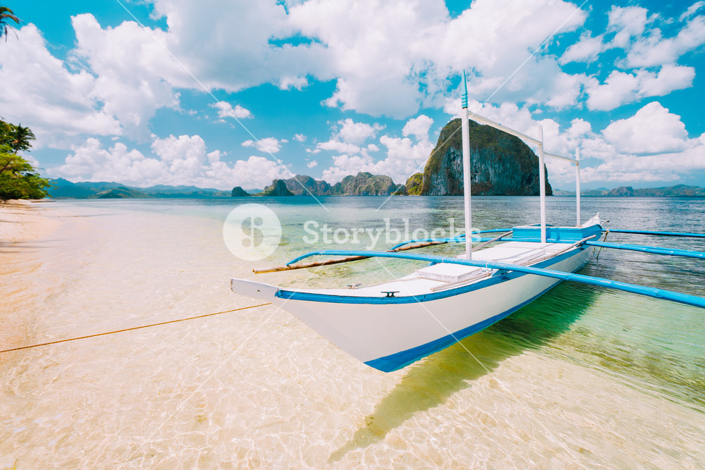 White banca island hopping boat at Las cabanas beach with amazing Pinagbuyutan island in background. Beautiful landscape scenery in El Nido, Palawan, Philippines