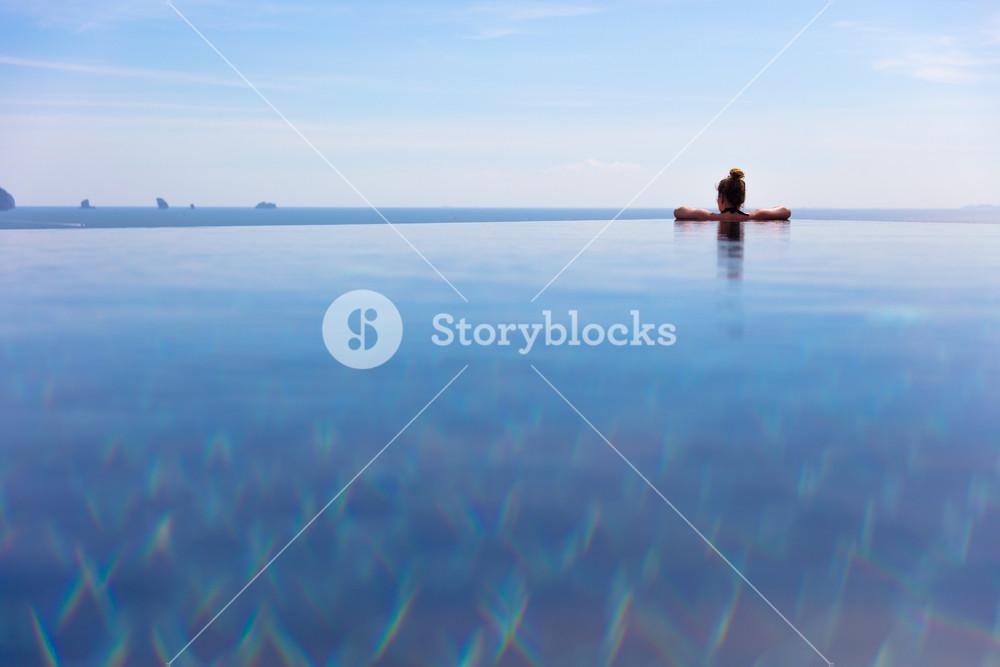 Woman Resting In Infinity Pool At a Aonang Beach Resort