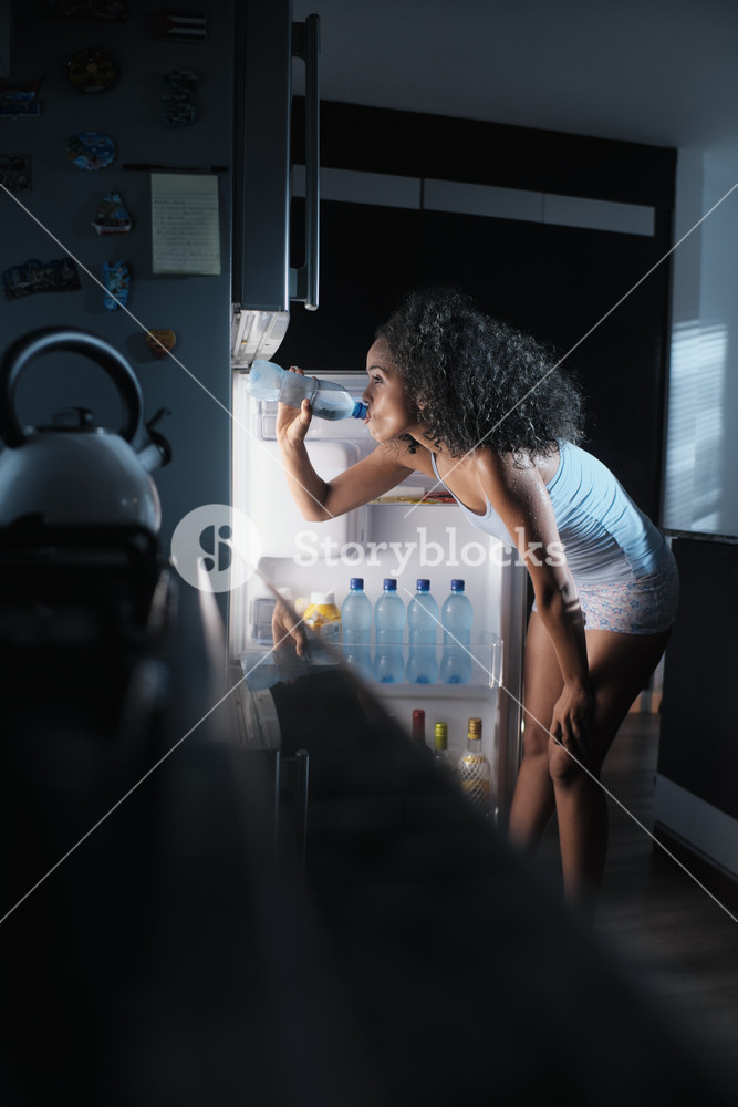 Young African American woman suffering for summer heat and lack of air conditioning at home. Black girl covered with sweat drinking fresh water from fridge.