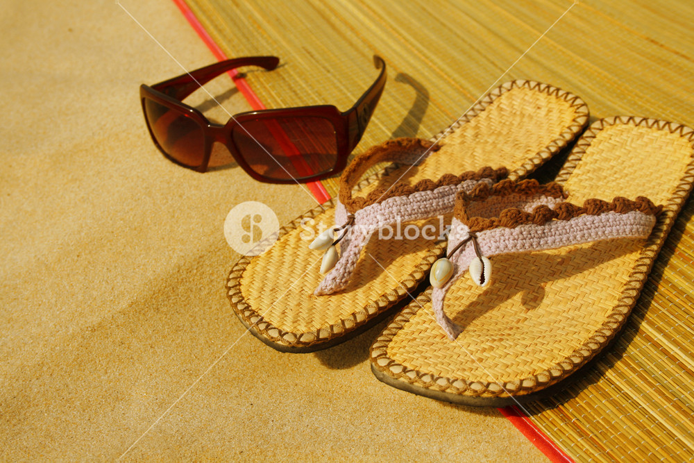 Sunglasses And Flip Flops On The Beach