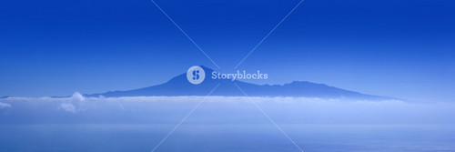 Sunlit lake and distant, foggy mountains