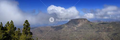 Sunlit, rocky cliffs under a cloudy sky