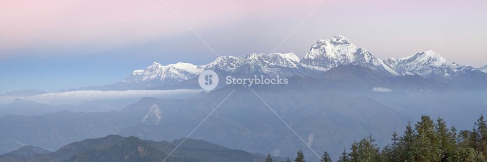 Sunlit, snow-capped mountain range at dawn