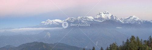 Sunlit, snow-capped mountain range at dawn
