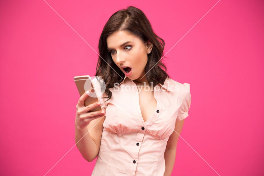 Surprised woman using smartphone
