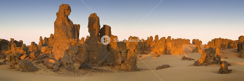 Tall rock formations in a sandy desert at sunset