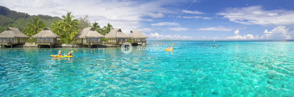Thatched huts and kayaks in the tropical ocean