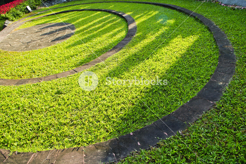 The Stone block walk path in the garden with green grass background