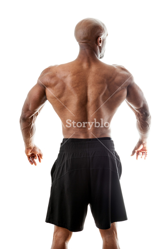 Toned and ripped lean muscle fitness man standing in front of a white background.