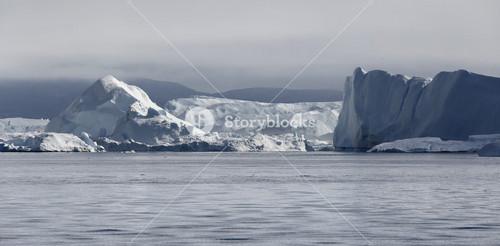Towering icebergs under a grey sky along a foggy coast
