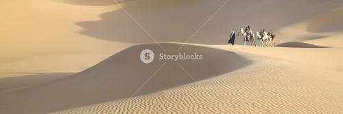 Travelers on camelback through a sandy desert