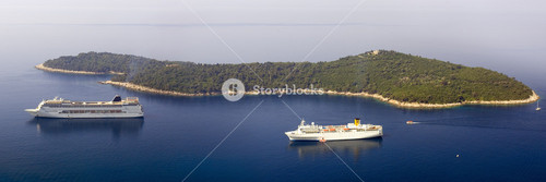 Two cruise ships and a sunlit, forested island