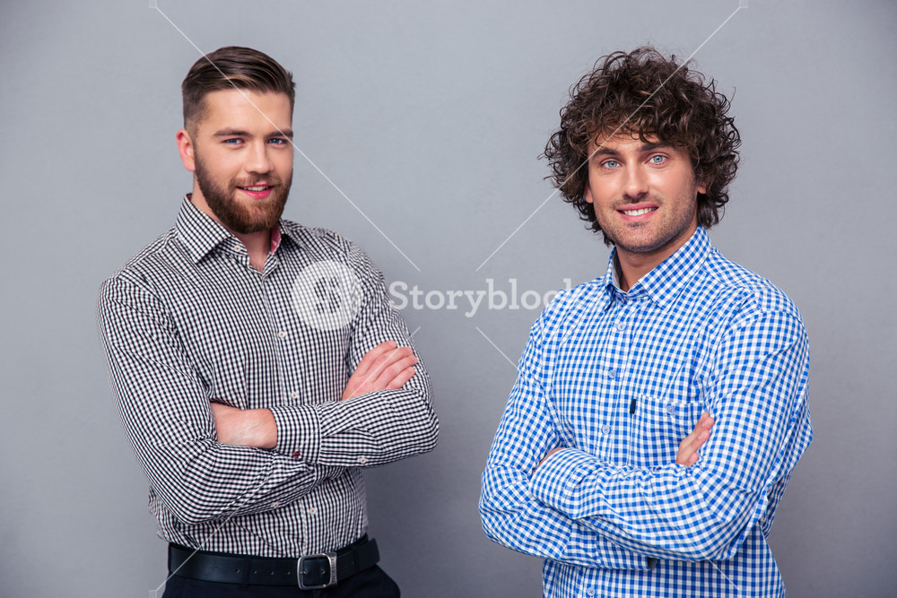 Two happy men standing with arms folded