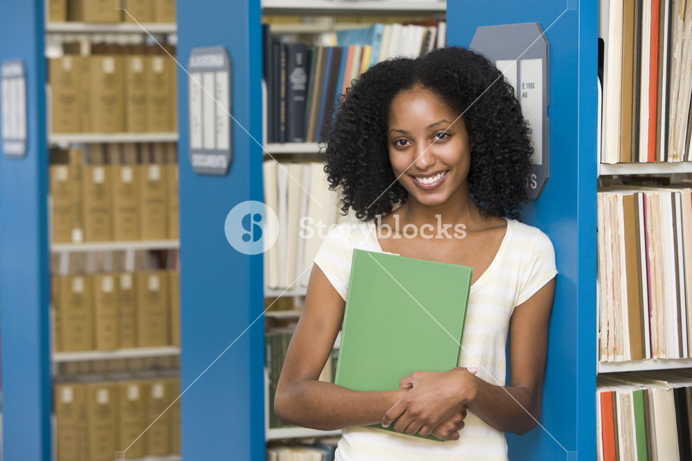 University student holding book in library